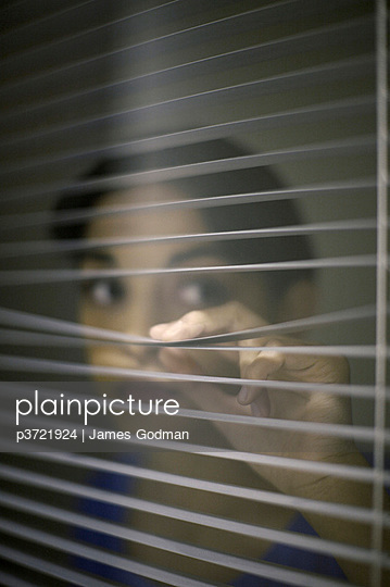 Young woman peering through blinds - p3721924 by James Godman
