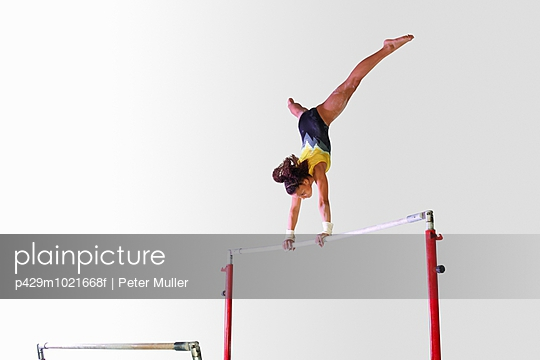 Young gymnast performing on uneven bars - p429m1021668f by Peter Muller