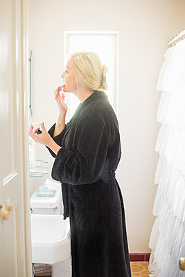 Blond woman standing in a bathroom, applying cream to her lips. - p1100m1080242 by Mint Images
