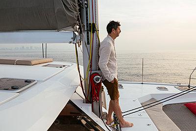 Marure man on catamaran, looking ta view - p300m2012490 von Bonninstudio