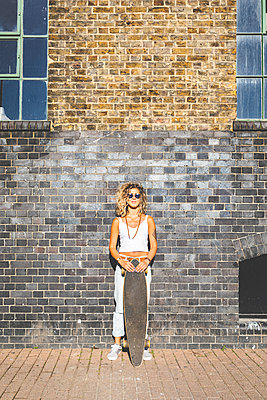Young woman standing with skateboard at brick wall in the city - p300m2063021 by William Perugini