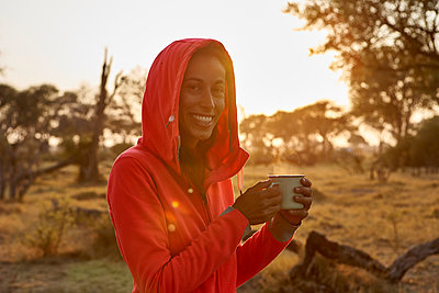 Woman having a coffee at sunrise, Khwai, Botswana - p300m2155873 by Veam