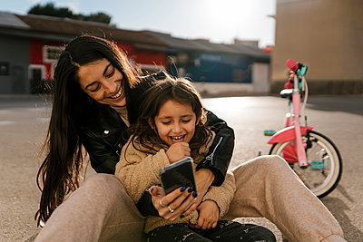 Smiling mother using mobile phone while sitting on road - p300m2265312 by Ezequiel Giménez