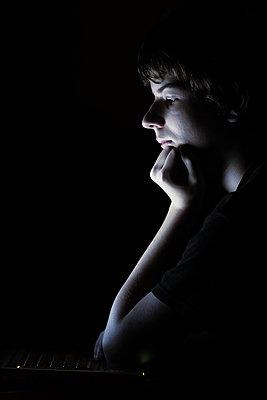 Junge im Dunkeln vor dem Computer - p719m2164399 von Rudi Sebastian