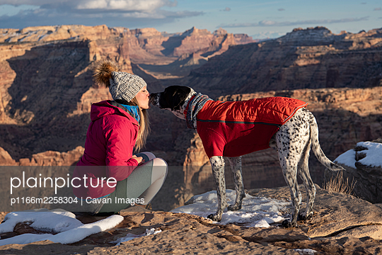 Woman kissing dog on mountain during vacation - p1166m2258304 by Cavan Images