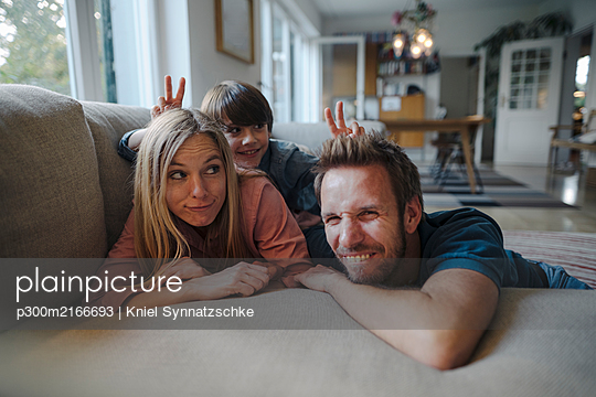 Happy family lying on couch, son making fun of his parents - p300m2166693 by Kniel Synnatzschke
