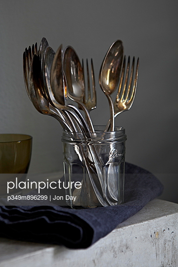 Vintage silver spoons and forks in a jamjar with denim napkin - p349m896299 by Jon Day