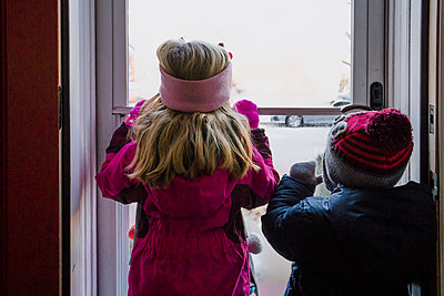 Two children dressed in winter clothing look out a door at snow. - p1166m2147026 by Cavan Images