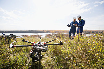 Surveyors with drone equipment on sunny hilltop overlooking lake - p1192m1194112 by Hero Images