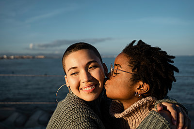 Young woman kissing friend while sitting against sea - p300m2243412 by Rafa Cortés