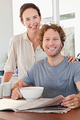 Couple reading newspaper at breakfast - p429m800863f by Hybrid Images