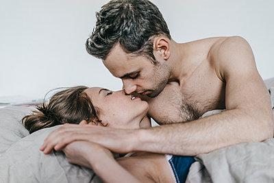 Junges Paar im Bett küsst sich - p586m1178733 von Kniel Synnatzschke