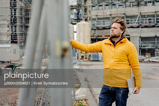 Man holding laptop, construction site in the background - p300m2004621 von Kniel Synnatzschke