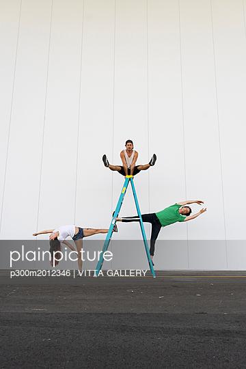 Three acrobats doing tricks on a ladder - p300m2012346 von VITTA GALLERY