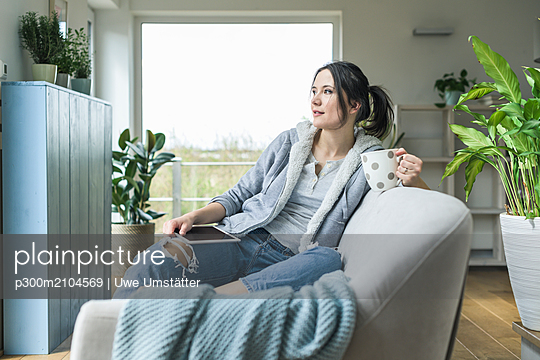 Pensive woman with a mug and tablet sitting on the couch at home - p300m2104569 von Uwe Umstätter