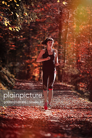 Woman jogging in autumn forest - p300m2166366 by Studio 27