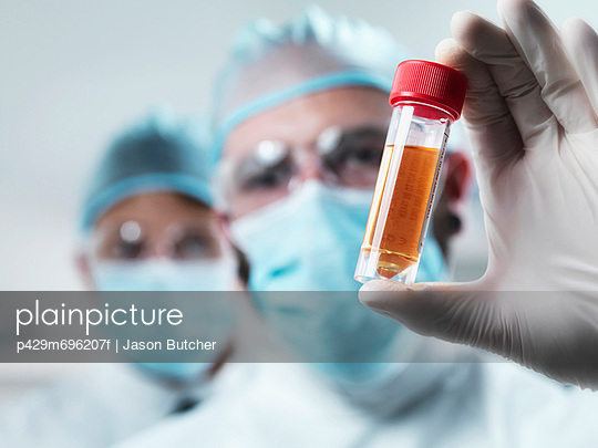 Scientist examining test tube in lab - p429m696207f by Jason Butcher
