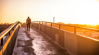 Man walking toward the sun at sunset on footbridge with backpack - p1166m2096553 by Cavan Images