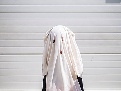 Child dressed as a ghost with house clothes - p1166m2124132 by Cavan Images