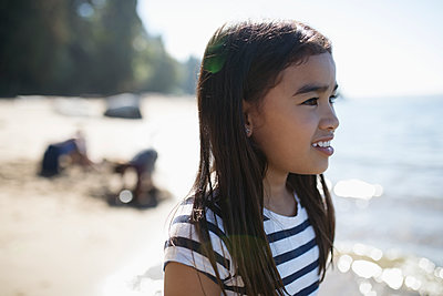 Smiling girl looking away on sunny beach - p1192m1511848 by Hero Images