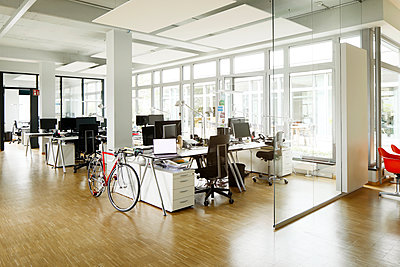 Bicycle at desk in open plan office - p300m2267873 by Peter Scholl