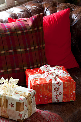 Two gift wrapped presents on brown Chesterfield sofa  Sussex  UK - p3493518 by Robert Sanderson
