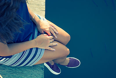 Woman sat on the pier  - p794m1064260 by Mohamad Itani