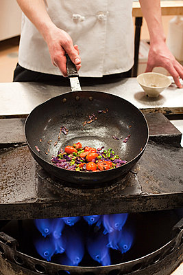 Male chef frying with wok in commercial kitchen - p9244361f by Image Source
