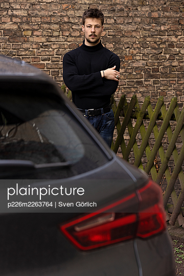 Young man by his car - p226m2263764 by Sven Görlich