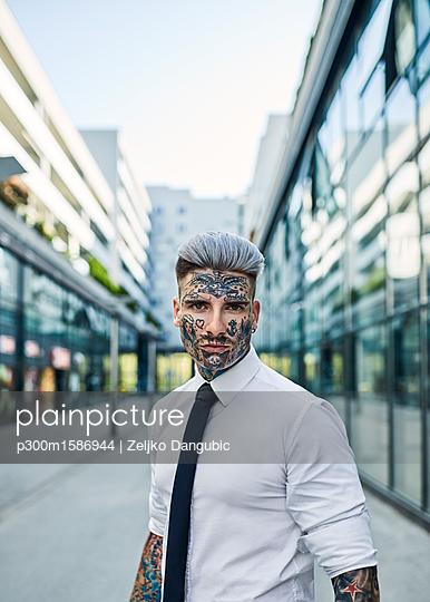 Young businessman with tattooed face walking in the city, portrait - p300m1586944 von Zeljko Dangubic