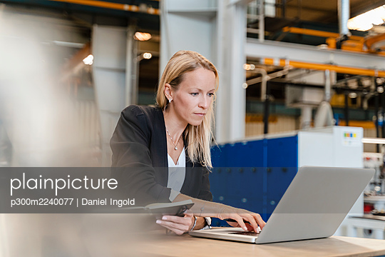 Female entrepreneur working on laptop while sitting in factory - p300m2240077 by Daniel Ingold