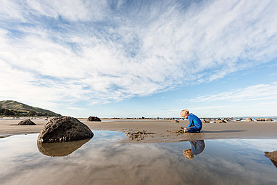 Boy playing in sand at beach with blue sky and reflection - p1166m2159468 by Cavan Images