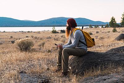 USA, North California, bearded young man having a break on a hiking trip near Lassen Volcanic National Park - p300m2059013 by Kike Arnaiz