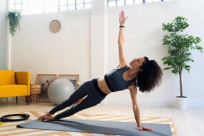 WOman doing yoga or fitness at home - p300m2274615 von Giorgio Fochesato