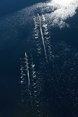 Elevated view of two rowing eights in water - p300m982198f by zerocreatives