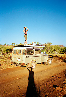 A woman taking a picture on top of an off-road vehicle, Australia - p3011587f by fStop