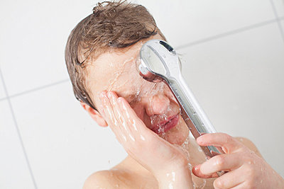 Young boy bathing with shower head in bathroom - p426m663138f by Katja Kircher