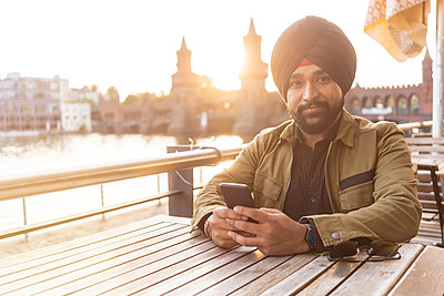 Indian man using smartphone in cafe by river, Berlin, Germany - p429m2077823 by Tamboly