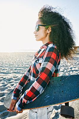 Hispanic woman holding skateboard at beach - p555m1303381 by Peathegee Inc