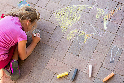 Caucasian girl drawing with chalk on brick - p555m1453235 by Marc Romanelli