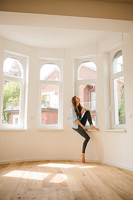 Young woman sits by window of new apartment - p586m1064869 by Kniel Synnatzschke
