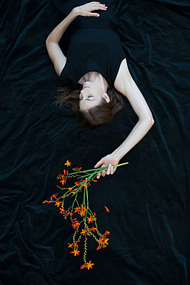Woman lying down holding flowers - p920m1573734 by Jude Mooney