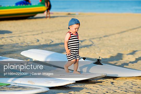 Cute little kid on a beach walking barefoot along windsurfing board - p1166m2250681 by Cavan Images