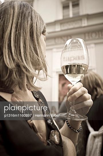 Blonde Frau mit Weinglas wendet sich ab, Linz, Oberösterreich, Österreich - p1316m1160397 von Hermann Erber