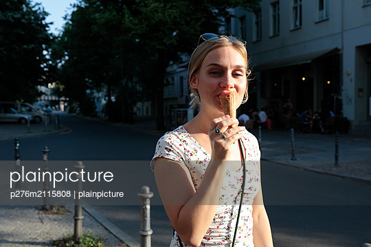 Young woman enjoys an ice cream in the evening sun - p276m2115808 by plainpicture