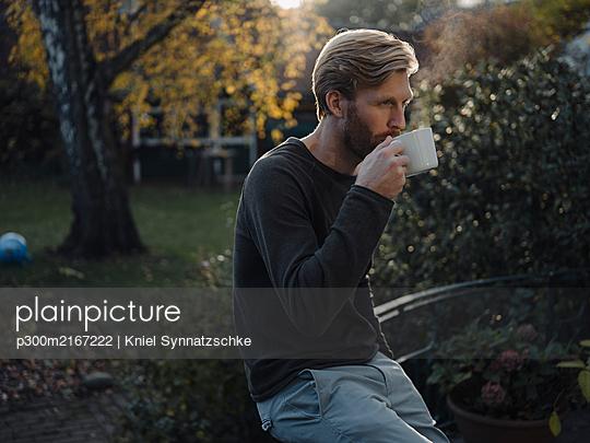 Man having a coffee break in garden - p300m2167222 by Kniel Synnatzschke