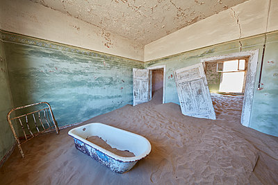 A view of a bathroom in a derelict building full of sand. - p1100m1489974 by Mint Images
