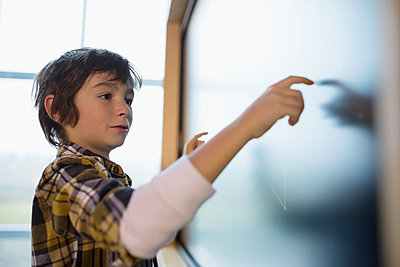 Boy using touch screen in science center - p1192m1194246 by Hero Images