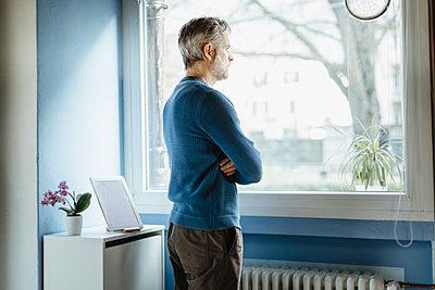 Pensive man standing in living room looking out of window - p300m2180934 by 27exp