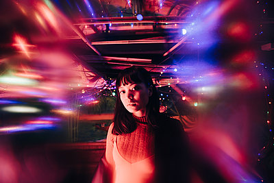 Portrait of young woman standing amidst illuminated multi colored lights at bar - p426m2205189 by Maskot